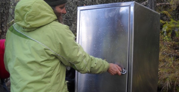 Tikwalus Heritage Trail - Kelley Demonstrates food cache box lock at campsite. Kelley Cook demonstrates caribeener lock mechanism. Food cache was custom built by a Chilliwack metal fabricator, using aluminum to reduce weight.