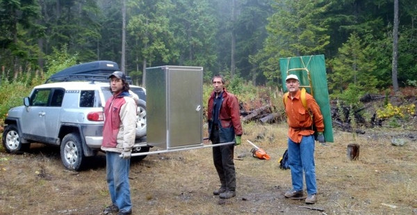 Tikwalus Heritage Trail - Hiking up supplies. Crew carries aluminum bear-proof food cache into campsite at the top of Lake Mtn. Green board will form the base of an interpretive kiosk on the Bluffs Viewpoint.